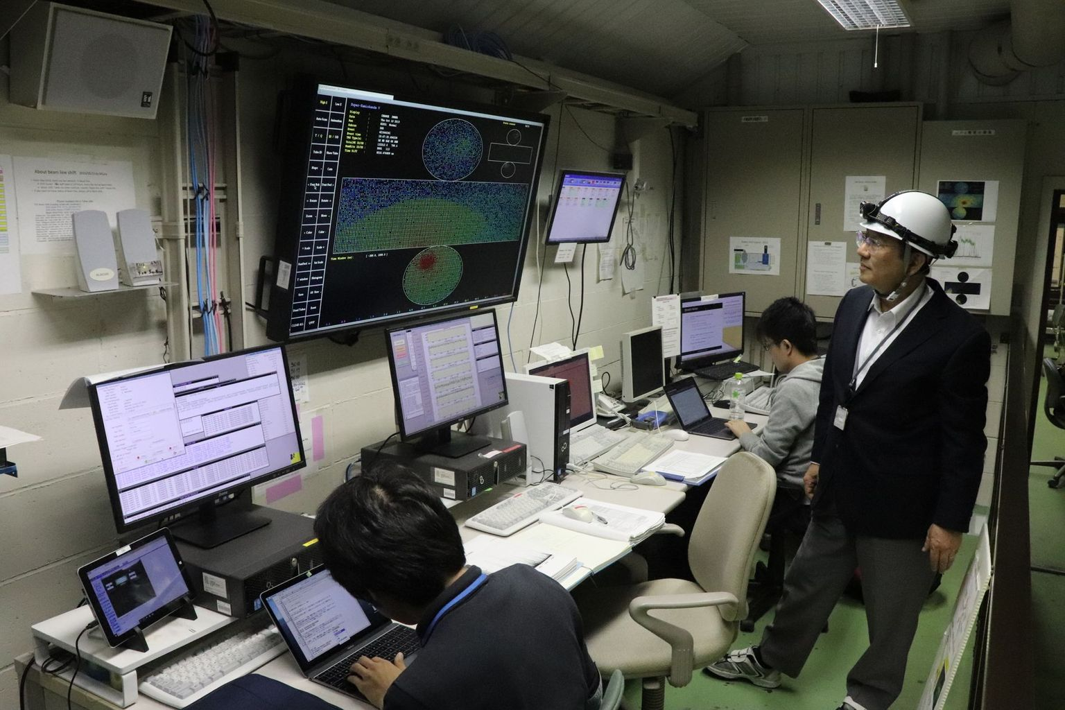 In the control room of the Super-Kamiokande. The large screen shows a current cosmic-ray event. Photo: B. Vogel