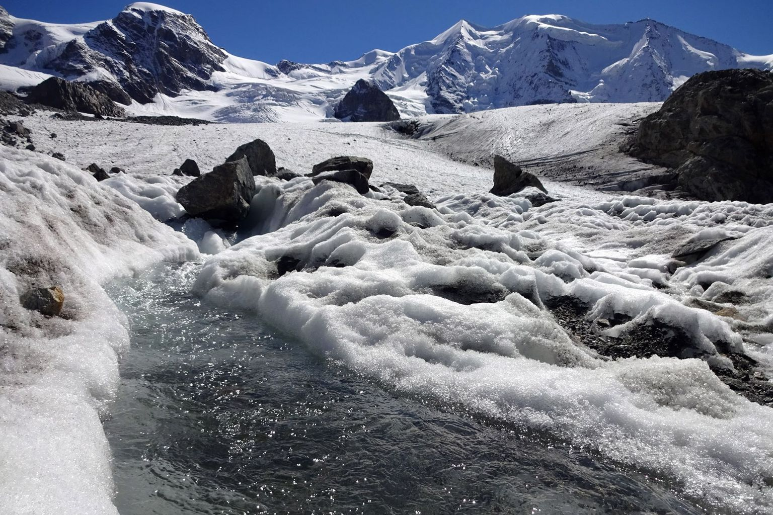 Meltwater streams on the Pers Glacier (GR). The summit regions are shining white as early as September due to fresh snow.