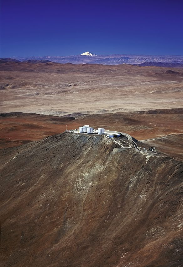 Aerial photograph of the home of ESO's Very Large Telescope (VLT) on Mount Paranal in Chile. The Paranal Observatory with its four giant 8.2-metre Unit Telescopes of the VLT is located at an altitude of 2,600 metres in the Atacama desert. In the background we can see the 6,720 metres-high volcano Llullaillaco, located a mind-boggling 190 km further East.