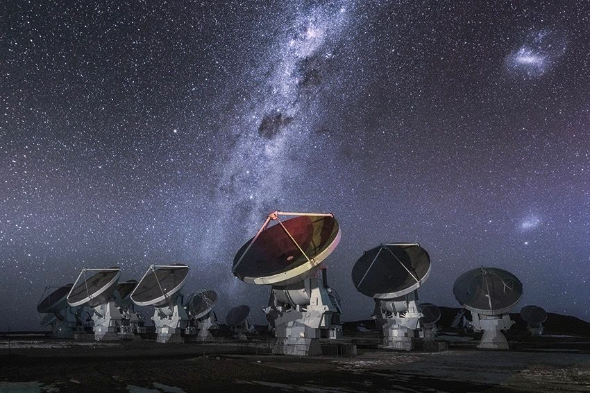 The Atacama Large Millimetre/submillimeter Array (ALMA) antennas work in tandem to form one large telescope. Some of the antennas in this image all point toward the same direction. The brightly shinning Milky Way Galaxy shoots through the sky in the background.